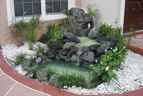 carved stone fountain spills into a small entryway pond